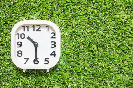 pm: Closeup white clock for decorate show a half past ten or 10:30 a.m. on green artificial grass floor textured background with copy space