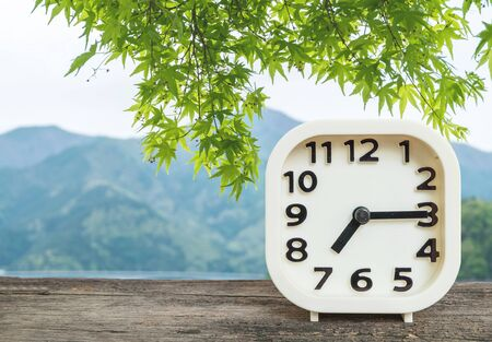 Closeup white clock for decorate show a quarter past seven or 7:15 a.m. on blurred mountain view background