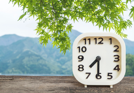 pm: Closeup white clock for decorate show half past seven oclock or 7:30 a.m. on blurred mountain view background