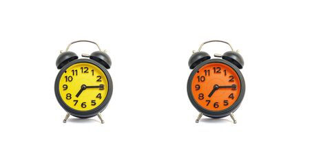 Closeup yellow alarm clock and orange alarm clock for decorate show a quarter past seven or 7:15 a.m. isolated on white background