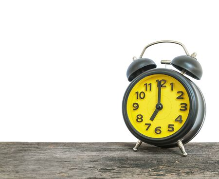 Closeup black and yellow alarm clock for decorate in 7 oclock on old brown wood desk isolated on white background with copy space