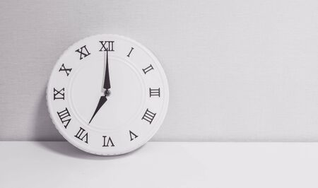 Closeup white clock for decorate in 7 oclock on white wood desk and wallpaper textured background in black and white tone with copy space