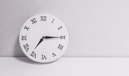 Closeup white clock for decorate show a quarter past seven or 7:15 a.m. on white wood desk and wallpaper textured background in black and white tone with copy space