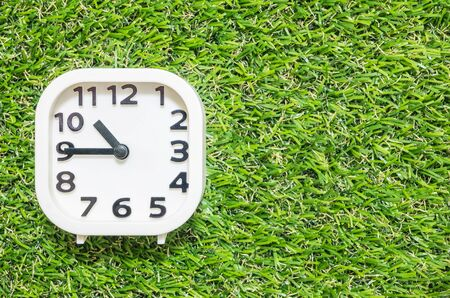 Closeup white clock for decorate show a quarter to eleven oclock or 10:45 a.m. on green artificial grass floor textured background with copy space