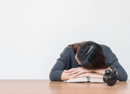 Asian woman sleep by lied on desk after she tired from reading book on blurred brown wooden desk and white cement wall textured background in work concept with copy space