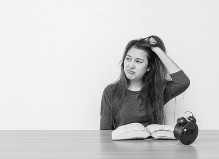 Closeup asian woman sitting for read a book with strain face emotion on wood table and white cement wall textured background in black and white tone with copy space