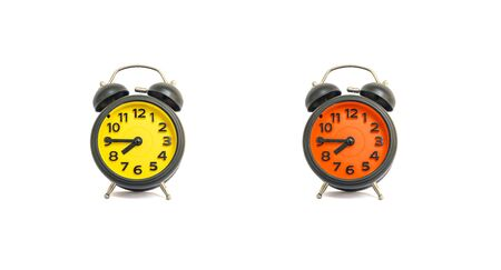 Closeup yellow alarm clock and orange alarm clock for decorate show a quarter to eight a.m. or 7:45 a.m. isolated on white background Stock Photo