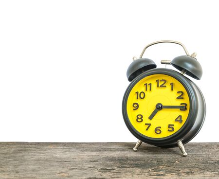 Closeup black and yellow alarm clock for decorate show a quarter past seven or 7:15 a.m. on old brown wood desk isolated on white background with copy space
