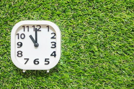 Closeup white clock for decorate in 11 oclock on green artificial grass floor textured background with copy space