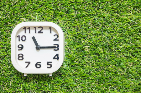 Closeup white clock for decorate show a quarter past eleven oclock or 11:15 a.m. on green artificial grass floor textured background with copy space Stock Photo