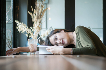 Closeup asian woman lied on the wooden counter desk for reading a book in coffee shop with happy face on blurred coffee shop view background under window light Stock Photo