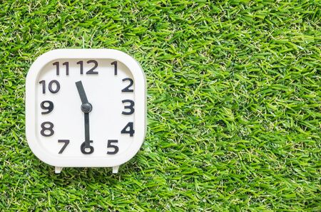 pm: Closeup white clock for decorate show a half past eleven or 11:30 a.m. on green artificial grass floor textured background with copy space
