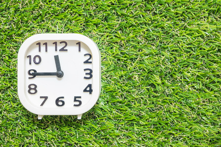 Closeup white clock for decorate show a quarter to twelve oclock or 11:45 a.m. on green artificial grass floor textured background with copy space