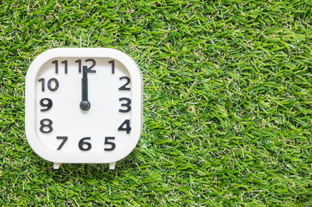 Closeup white clock for decorate in 12 oclock on green artificial grass floor textured background with copy space