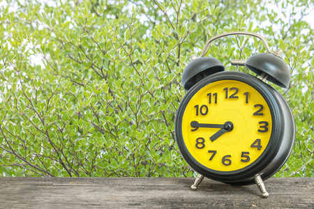 seven o'clock: Closeup black and yellow alarm clock for decorate show a quarter to seven oclock or 7:45 a.m. on old brown wood desk on green leaves in the park textured background Stock Photo