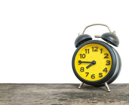 Closeup black and yellow alarm clock for decorate show a quarter to eight oclock or 7:45 a.m. on old brown wood desk isolated on white background with copy space