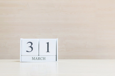 Closeup surface white wooden calendar with black 31 march word on blurred brown wood desk and wood wall textured background with copy space , selective focus at the calendar Stock Photo