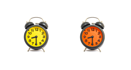 Closeup yellow alarm clock and orange alarm clock for decorate show a half past eight oclock or 8:30 a.m. isolated on white background Stock Photo