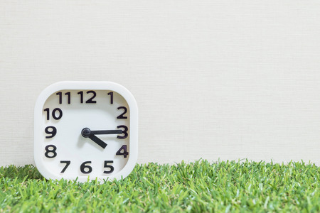 number 15: Closeup white clock for decorate show a quarter past four oclock or 4:15 p.m. on green artificial grass floor and cream wallpaper textured background with copy space