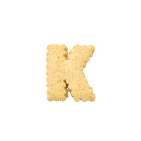 Closeup brown biscuit in K english alphabet isolated on white background with clipping path