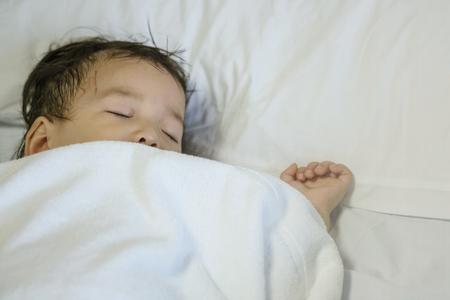 Closeup sick child sleep on hospital bed textured background
