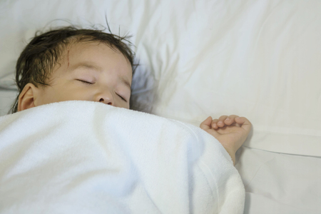 Closeup sick child sleep on hospital bed textured background