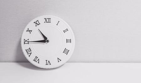 numero diez: Closeup reloj blanco para decorar mostrar un cuarto a las once en punto o 10:45 am en el escritorio de madera blanca y papel tapiz de fondo con textura en tono blanco y negro con copia espacio