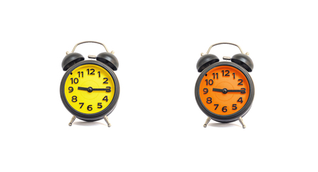 pm: Closeup yellow alarm clock and orange alarm clock for decorate show a quarter past nine oclock or 9:15 a.m. isolated on white background Stock Photo