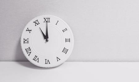Closeup horloge blanche pour décorer à heures sur bureau bois