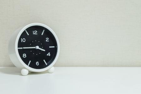 4 または 15:45 白い木製の机、コピー領域を持つ質感のクリームの壁紙の背景の四分の一での黒と白のクローズ アップ目覚まし時計を飾る 写真素材