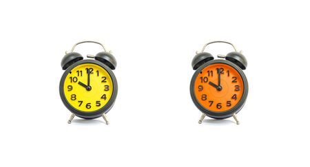 pm: Closeup yellow alarm clock and orange alarm clock for decorate in 10 oclock isolated on white background