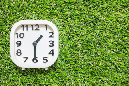 Closeup white clock for decorate show a half past one oclock or 1:30 p.m. on green artificial grass floor textured background with copy space Stock Photo