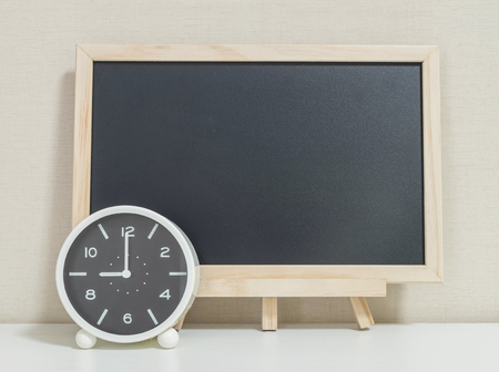 Closeup alarm clock for decorate show 9 o'clock with wood black board on white wood desk and cream wallpaper textured background , selective focus at the clock