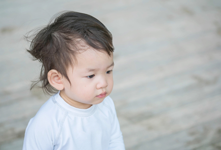 puerile: Closeup cute asian kid interest in something emotion with copy space