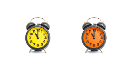 pm: Closeup yellow alarm clock and orange alarm clock for decorate in 11 oclock isolated on white background Stock Photo