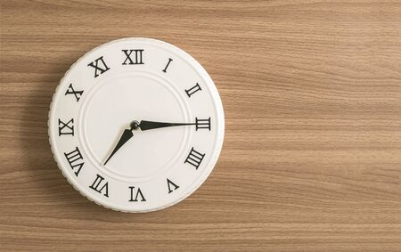 seven o'clock: Closeup white clock for decorate show a quarter past seven oclock or 7:15 a.m. on wood desk textured background with copy space