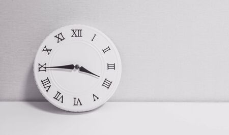 Closeup white clock for decorate show a quarter to four oclock or 3:45 p.m. on white wood desk and wallpaper textured background in black and white tone with copy space