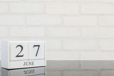 Closeup white wooden calendar with black 27 june word on black glass table and white brick wall textured background with copy space in selective focus at the calendar Banco de Imagens