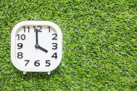 Closeup white clock for decorate in 4 oclock on green artificial grass floor textured background with copy space