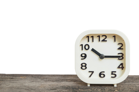 Closeup white clock for decorate show a quarter past ten oclock or 10:15 a.m. on old brown wood desk isolated on white background with copy space