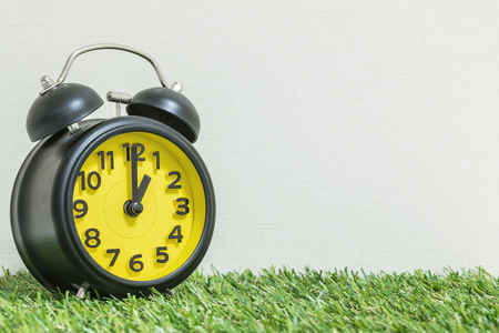 Closeup black and yellow alarm clock for decorate in 1 oclock on green artificial grass floor and cream wallpaper textured background with copy space