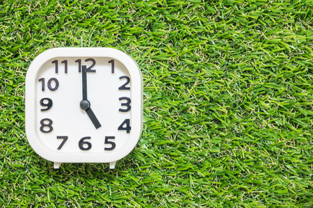 Closeup white clock for decorate in 5 oclock on green artificial grass floor textured background with copy space