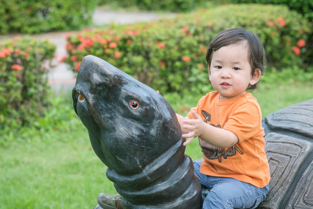 puerile: Closeup cute asian kid sit on turtle statue in the park background Stock Photo