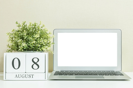 White wooden calendar with black 8 august word with white blank space at center of computer notebook on white wood desk and cream wallpaper textured background , selective focus at the calendar Stock fotó