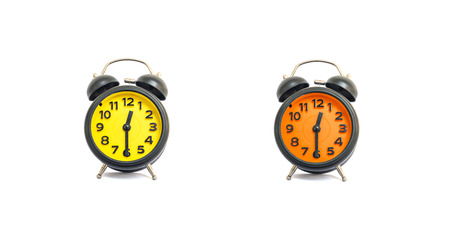 Closeup yellow alarm clock and orange alarm clock for decorate show a half past twelve oclock or 12:30 p.m. isolated on white background Stock Photo