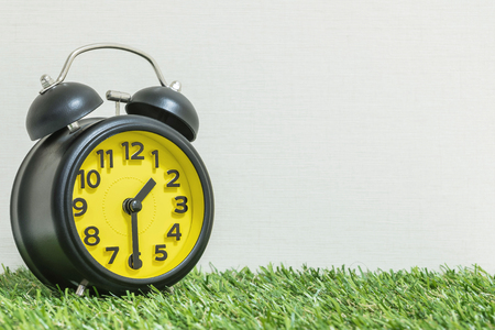 Closeup black and yellow alarm clock for decorate show half past one oclock or 1:30 p.m. on green artificial grass floor and cream wallpaper textured background with copy space