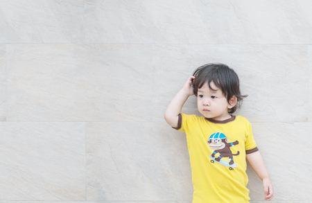 Closeup cute asian kid look at the space with confuse motion on marble stone wall textured background Stock Photo