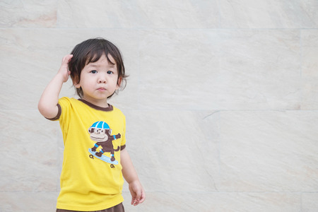 Closeup cute asian kid with confuse motion on marble stone wall textured background with copy space