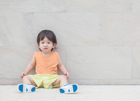 puerile: Closeup happy asian kid with smile face sit on marble stone floor and wall textured background with copy space Stock Photo