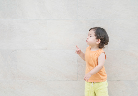 puerile: Closeup cute asian kid point to copy space of picture on marble stone wall textured background
